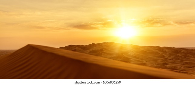 a sandy desert barkhans at sunset