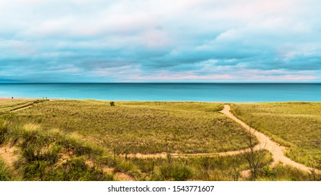 Sandy dunes and grass in New Buffalo, Michigan on the lake.  Dramatic sky front coming in before it rains on multiple sandy paths leading to the beach.