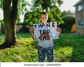 Sandy, England - 07.05.2020: A young boy holds a rainbow drawing and the Thank You message for the medical staff working through the Covid-19 Pandemic