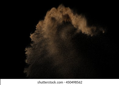 Sandy explosion isolated on black background. Abstract sand cloud.