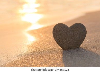 Sandy heart shape silhouette at sunset sea beach, valentines day, wedding, honeymoon or love greeting card concept