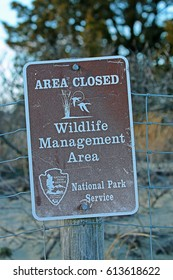 """SANDY HOOK, NEW JERSEY/USA - FEBRUARY 11, 2017: A brown and white National Park Service (Department of the Interior) sign designating the """"Area Closed - Wildlife Management Area."""""""