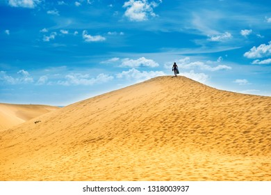 Sandy landscape with woman on top of dune. Natural reserve Maspalomas Dunes, Gran Canaria, Spain