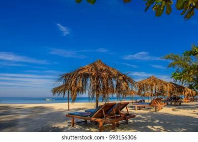 Sandy Ngapali beach, Myanmar. Chairs with umbrella.