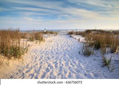 Sandy path with footprints leading to the Atlantic Ocean on Folly Beach near Charleston, South Carolina.