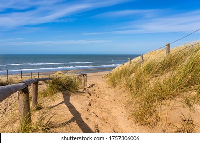 Sandy path over a dune with a fence in the sun with a view over the North Sea in Noordwijk, Netherlands