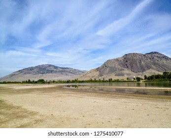 The sandy river bank of the North Thompson river in the beautiful dry landscape of Kamloops, British Columbia, Canada.  A great spot for locals walk go swimming.