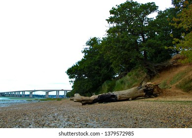 A sandy riverbank with Orwell Bridge in the background