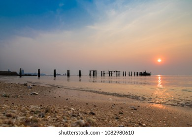 The sandy seascape of the seashore and the structure of the old wooden bridge stretch into the sea. The sky is bright and the sun is falling. In the evening