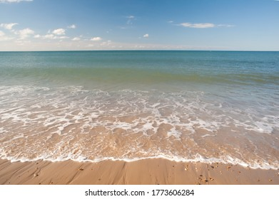 sandy seaside beach blue sky a few clouds and colour in the sea at bournemouth in dorset southcoast of uk