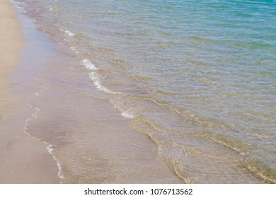 sandy shore and small ripples on water natural background