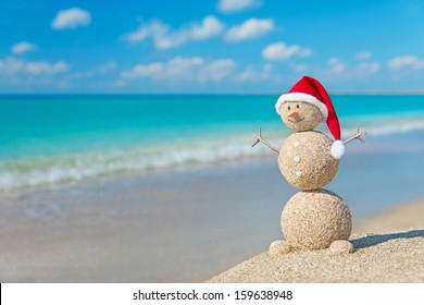 Sandy snowman in red santa hat at tropical ocean beach. Holiday concept for New Years and Christmas Cards.