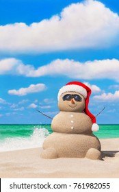 Sandy snowman in red Santa hat and sunglasses at tropical ocean sunny beach against waves splashes. Happy New Year and Merry Christmas travel destinations concept for tropical vacation