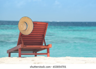 Sandy tropical beach with deck chairs in sunny day. Summer holiday and vacation concept.