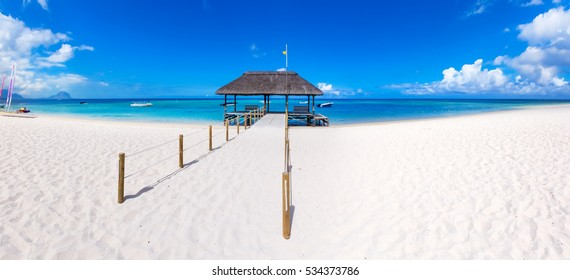Sandy tropical Wolmar beach at sunny day. Jetty on the foreground.  Mauritius. Panorama
