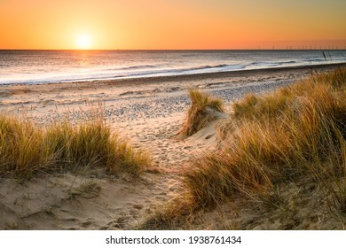 A sandy winding path weaves through the sand dunes and towards the sea on the Norfolk Coast at Winterton on Sea as the early morning sun rises above the horizon.