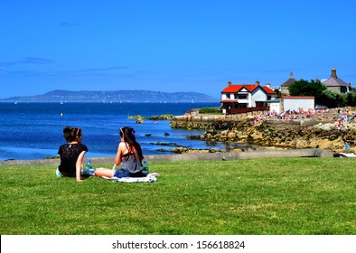 SANDYCOVE, IRELAND - CIRCA JULY 2013: Two unidentified women sit in sunshine along the Sandycove coastline circa July, 2013 in Sandycove, Ireland.