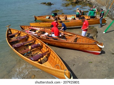 SANDYCOVE, IRELAND - JUNE 15: Unidentified competitors and beached wooden racing skiffs at The East Coast Rowing Council Races on June 15, 2014 in Sandycove, Ireland.