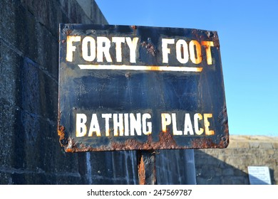 SANDYCOVE, IRELAND - OCTOBER 18: The rusty, hand painted main signpost at the entrance to the famous Forty Foot bathing place on October 18, 2014 in Sandycove, Ireland.