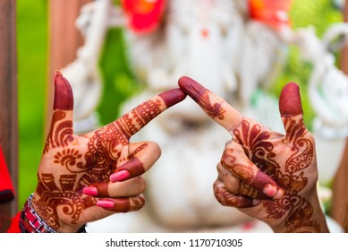 Sanga, Nepal - July 16, 2018 : Image of henna painted women hands in Sanga, Nepal. Two women keeping their poining fingers one against the other. Henna details, Ganesha hindu god statue in background