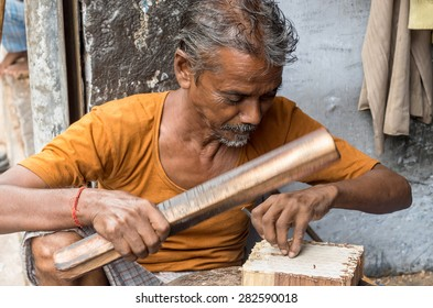 SANGANER, INDIA - SEPTEMBER 11, 2014: Unidentified craftsman carving a wooden printing block for textile block printing