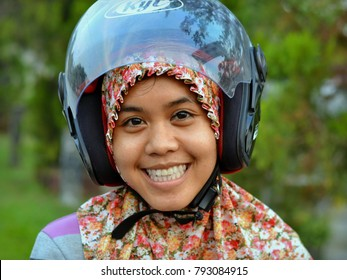 SANGGAU, INDONESIA - SEP 24, 2013: Young Indonesian woman from West Kalimantan with modern motorcycle helmet over her traditional hijab smiles and poses for the camera, on Sep 24, 2013.