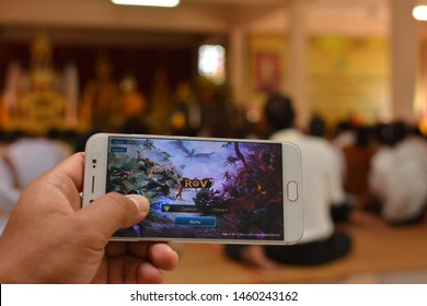 Sangkha , Surin / Thailand - July 18 2019 : People use smartphone to play ROV GAME (AOV) during a religious ceremony. Concept of  people who just don't care about religion.