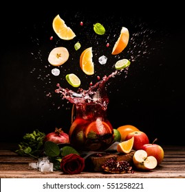 Sangria. Flying fruits. Apple, orange, lime, pomegranate, mint. Drink. Wine. Concept. Dark moody. Spain. Beverage jug. Juice jar.