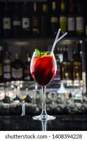 Sangria in a glass closeup in the bar. Cold summer homemade fruit and berries lemonade. Mojito, lemonade or sangria in glass. On dark background