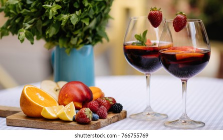 Sangria in glasses with ingredients - orange, lemon and lime slices and mint