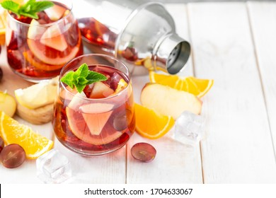 Sangria and ingredients in glasses on wood background, copy space