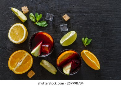 Sangria ingredients - orange, lemon, lime, apple slices, mint, sugar on dark stone background, top view