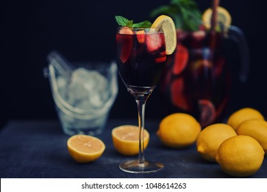 Sangria and ingredients. Refreshing sangria or punch with fruits in wine glasses and pitcher. Red wine sangria with ice. Tradbcional spanish  sangria on the rustic wooden table, copy space.