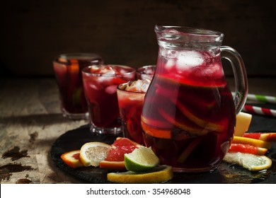 Sangria in pitcher with slices of fruit and ice, selective focus
