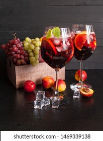 Sangria red wine or punch with fruit and ice in glasses. Homemade refreshing sangria fruit on a rustic wooden table. Spanish cuisine.