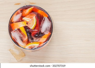 Sangria wine in the wineglass and pieces of ice on wooden table