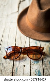 sanhat and sunglasses lying on shabby wooden table in daylight.
