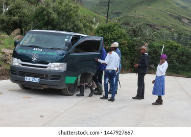Sani Pass, Lesotho - February 26, 2019: Local men and women queue to commute with an informal taxi stopping by the side of the road.