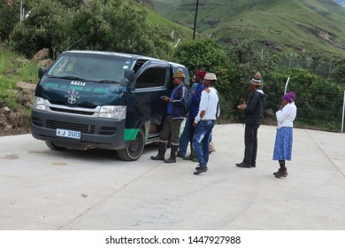 Sani Pass, Lesotho - February 26, 2019: Male and female local workers queue to commute with an informal taxi stopping in the road.
