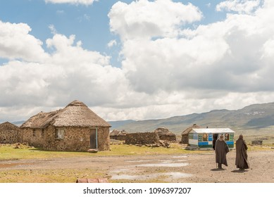 SANI TOP, LESOTHO - MARCH 24, 2018: Two Basotho men in front of a craft shop and stone huts at the Lesotho Border Post at the top of the Sani Pass