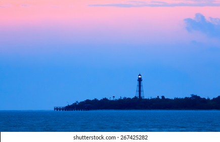 The Sanibel Island Lighthouse, also know as the Point Ybel Light, shines its light in the early morning as the rising sun paints the sky pink.