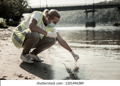 Sanitary inspection. Experienced worker of sanitary inspection service sitting near the river while checking water in the river