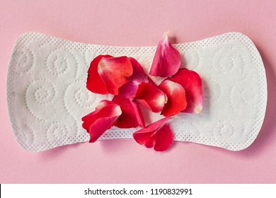 Sanitary napkin and flower petals on pink background, selective focus. Feminine hygiene, protection during menstruation
