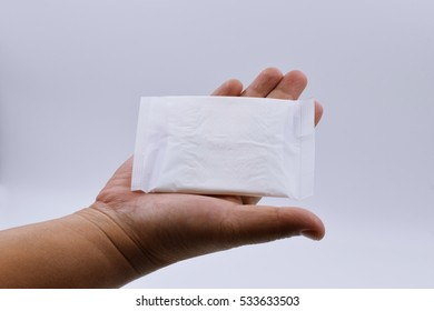 sanitary napkin in hand of woman on white background