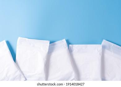 Sanitary pad, Sanitary napkin on blue background. Menstruation, Feminine hygiene, top view.