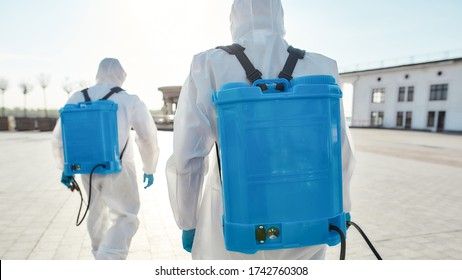 Sanitization and disinfection of the city due to the emergence of the Covid19 virus. Specialized team in protective suits and masks with backpack of pressurized spray disinfectant. Rear view