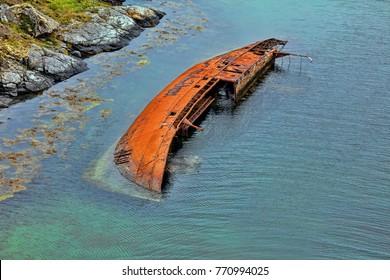 Sank ship wreckage by the rocky scandinavian coast