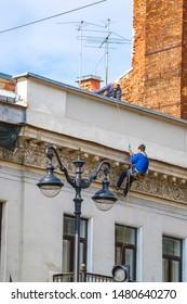 Sankt Peterburg, Russia - August, 13, 2019: steeplejack works on a house wall in Sankt Peterburg