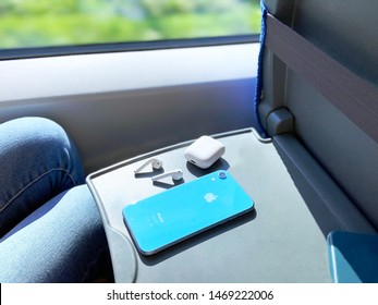 Sankt-Peterburg / Russia - 07.29.2019 Person in the train with his blue smartphone iPhone XR and wireless earphones apple AirPods looking at the window. Gadgets and traveling.