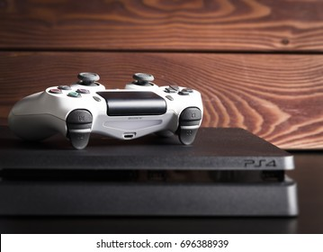 Sankt-Petersburg, Russia - 14 August, 2017: Sony PlayStation 4 Slim 1Tb revision and game controller on the wood background